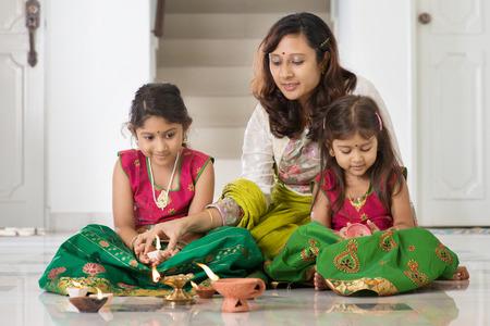 celebração: família indiana na lâmpada de óleo tradicional iluminação de sari e celebrando Diwali, fesitval de luzes em casa.