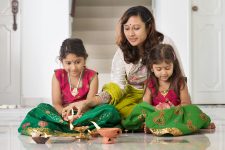 Indische familie in traditionele sari verlichting olielamp en vieren Diwali, fesitval van de lichten in huis.
