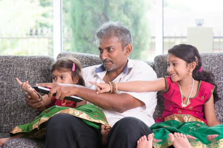 family movies: Happy Indian family watching tv together, switching channel with remote control, father and children indoor living lifestyle at home.