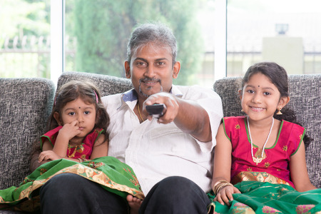 remote: Happy Indian family watching tv together, father and children indoor living lifestyle at home. Stock Photo