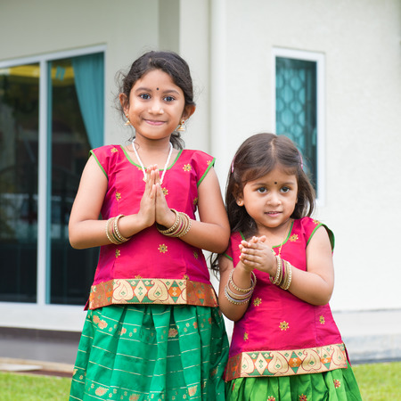 Cute Indian girls dressed in sari with folded hands representing traditional Indian greeting, standing outside their new house celebrating diwali, festival of lights. Stock Photo