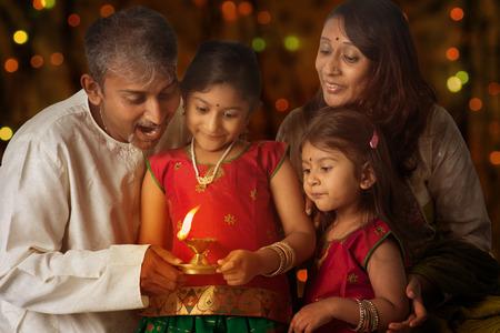 familia: Familia india en la lámpara de aceite de iluminación sari tradicional y la celebración de Diwali, fesitval de luces en el interior de un templo. Niña manos que sostienen la lámpara de aceite con el fondo hermoso del bokeh.