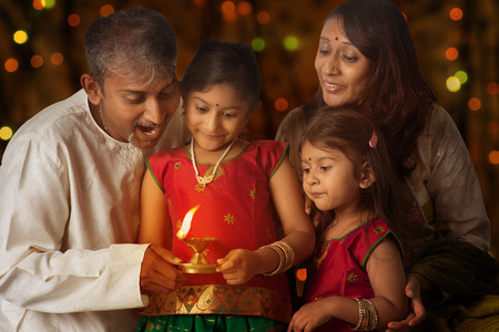 india culture: Indian family in traditional sari lighting oil lamp and celebrating Diwali, fesitval of lights inside a temple. Little girl hands holding oil lamp with beautiful bokeh background.
