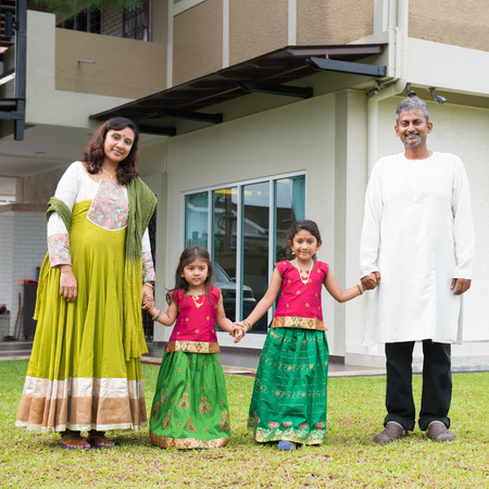 happy rich woman: Indian family in traditional dress saree holding hands standing outside their new home.