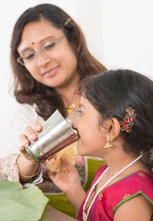 Indian family dining at home. Photo of child drinking water on dining table. Traditional home cook meal.