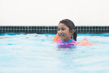 swimming to float: Asian girl in swimmer class with float bands. Indian child learning swimming in pool. Stock Photo