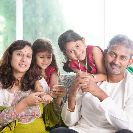 Happy Indian family at home. Asian parents with their kids, sitting on sofa. Parents and children indoor lifestyle.