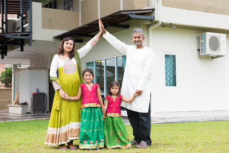 from the front: Parents forming house roof shape above children. Beautiful Asian Indian family portrait smiling and standing outside their new house.