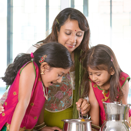 indian spice: Asian family cooking food together in kitchen. Indian mother and children preparing meal at home. Traditional India people with sari clothing.