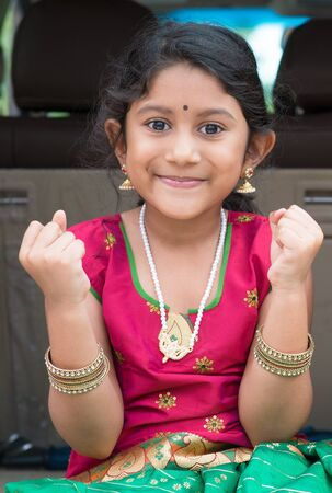 indian kid: Excited Indian girl sitting in car smiling, ready to vacation. Asian child in traditional dress. Stock Photo