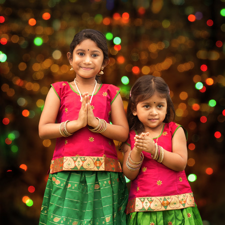 Cute Indian girls dressed in sari with folded hands representing traditional Indian greeting, standing inside a temple celebrating diwali, festival of lights.