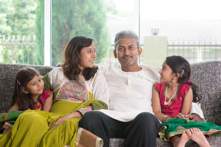 family sofa: Happy Indian family at home. Asian parents bonding with their kids, sitting on sofa. Parents and children indoor lifestyle. Stock Photo
