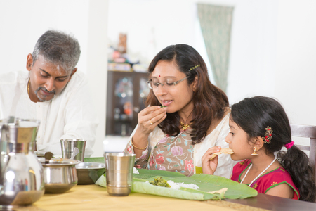 Indian family dining at home. Candid photo of India people eating rice with hands. Asian culture. Standard-Bild