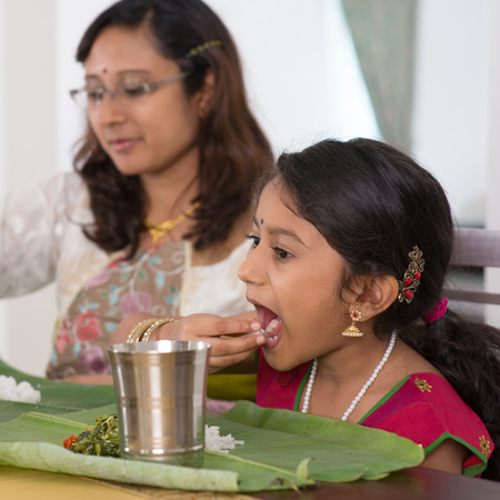 female child: Indian family dining at home. Candid photo of India people eating rice with hands.