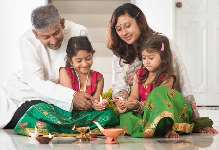Indian family in traditional sari lighting oil lamp and celebrating Diwali, fesitval of lights at home. Little girl hands holding oil lamp indoors. Stock Photo