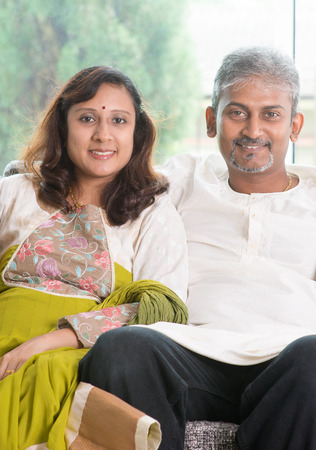 Indian couple. Portrait of mid age beautiful Indian family in traditional costume at home. Indian husband and wife indoor living lifestyle.