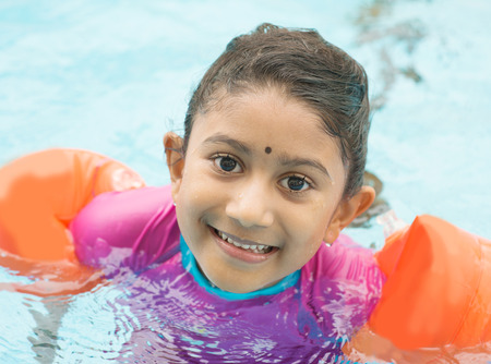 children learning: Indian child learning swimming in pool. Asian kid in swimmer class with float bands. Stock Photo