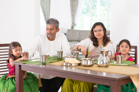 indoors: Indian family dining at home. Photo of Asian people eating rice with hands. India culture.