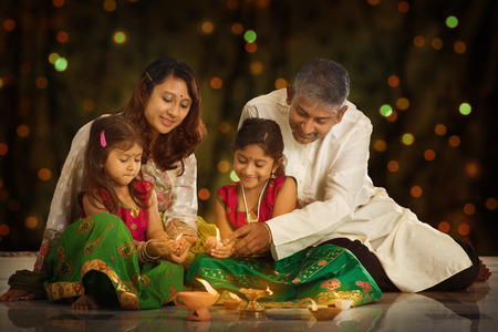 Indian family in traditional sari lighting oil lamp and celebrating Diwali or deepavali, fesitval of lights at home. Little girl hands holding oil lamp indoors.
