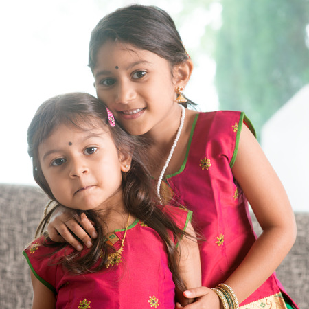 asian baby girl: Indian girl hugging her younger sister with love. Asian children at home. Beautiful daughters in traditional India sari. Stock Photo