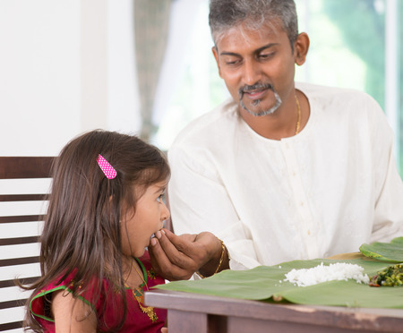 Indian family dining at home. Candid photo of India people eating rice with hands. Parent feeding child. photo