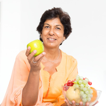 woman eating fruit: Old people healthy eating. Portrait of a 50s Indian mature woman eating fruits at home. Indoor senior people living lifestyle.