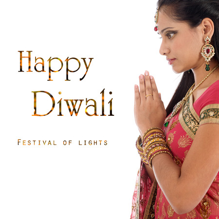 orando: Mujer india en sari tradicional orando y celebrando Diwali o Deepavali, fesitval de las luces en el templo. Manos de oraci�n Chica cruzados, aisladas sobre fondo blanco.
