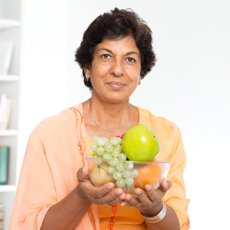 pakistani ethnicity: Old people healthy eating. Portrait of a 50s Indian mature woman holding fresh fruits at home. Indoor senior people living lifestyle. Stock Photo
