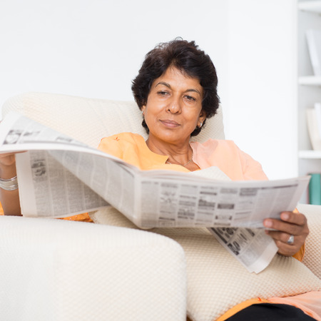life at home: Portrait of a 50s Indian mature woman reading newspaper, sitting on sofa at home. Indoor senior people living lifestyle.