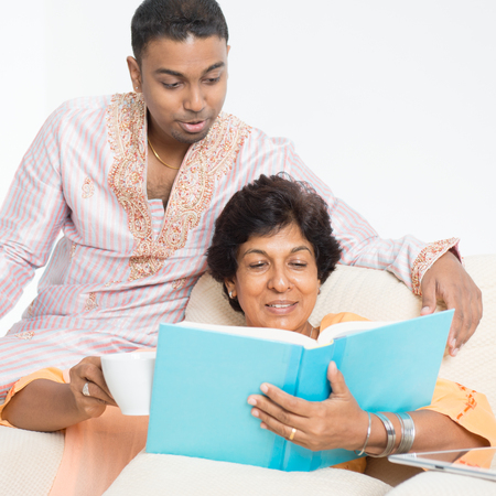 asian adult: Portrait of happy Indian family reading book, sharing hobby at home. Beautiful mature 50s Indian mother and her 30s grown son. Stock Photo
