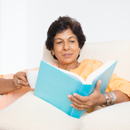 50s: Portrait of a 50s Indian mature woman reading book and drinking coffee at home. Indoor senior people living lifestyle.
