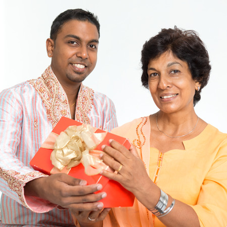 pakistani: Portrait of happy Indian family celebrate mothers day at home. Mature 50s Indian mother received surprised gift from her 30s grown son. Stock Photo