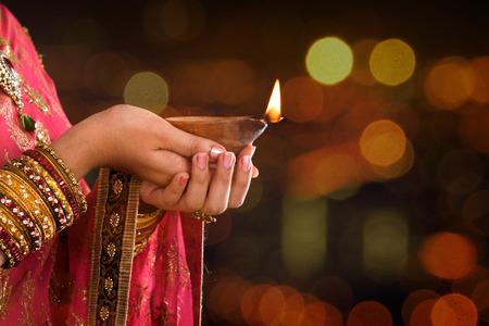 candil: Cierre de la mujer india en la lámpara tradicional de aceite de iluminación sari y la celebración de Diwali o Deepavali, fesitval de las luces en el templo. Manos femeninas que sostienen la lámpara de aceite, hermosas luces bokeh.