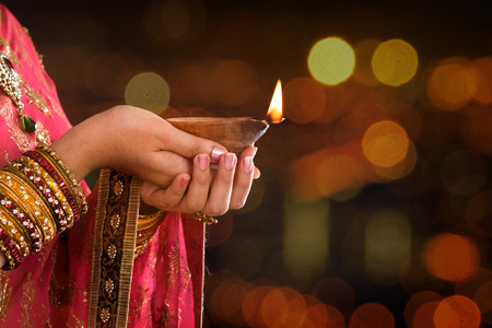 religious: Close up Indian woman in traditional sari lighting oil lamp and celebrating Diwali or deepavali, fesitval of lights at temple. Female hands holding oil lamp, beautiful lights bokeh background.
