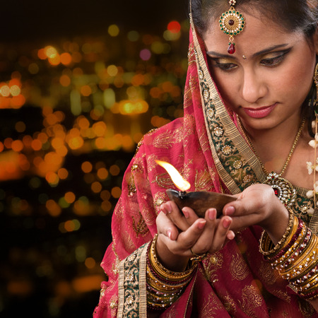 indian culture: Indian female in traditional sari lighting oil lamp and celebrating Diwali or deepavali, fesitval of lights at temple. Woman hands holding oil lamp, beautiful lights bokeh background.