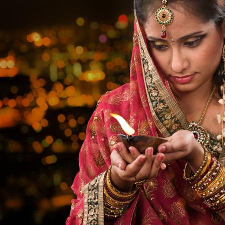 oil lamp: Indian female in traditional sari lighting oil lamp and celebrating Diwali or deepavali, fesitval of lights at temple. Woman hands holding oil lamp, beautiful lights bokeh background.