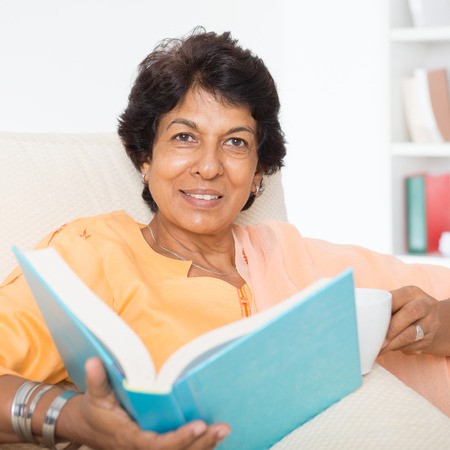 Portrait of a 50s Indian mature woman reading book and drinking coffee at home. Indoor senior people living lifestyle.