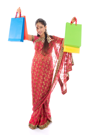 south asian ethnicity: Indian woman in traditional sari shopping for diwali festival, full length standing isolated on white background.