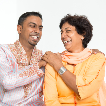 Portrait of happy Indian family having fun at home. Mature 50s Indian mother and 30s grown son laughing happily. Stock Photo