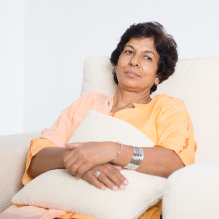 senior pain: Portrait of a tired 50s Indian mature woman resting on sofa at home. Indoor senior people living lifestyle. Stock Photo