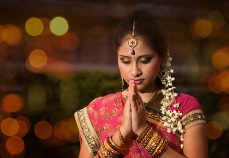 Indian female in traditional sari praying and celebrating Diwali or deepavali, fesitval of lights at temple. Girl prayer hands folded, beautiful lights bokeh background.