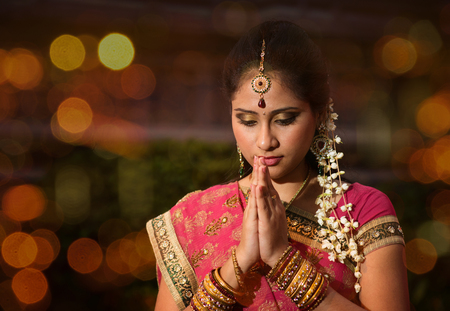indian saree: Indian female in traditional sari praying and celebrating Diwali or deepavali, fesitval of lights at temple. Girl prayer hands folded, beautiful lights bokeh background.