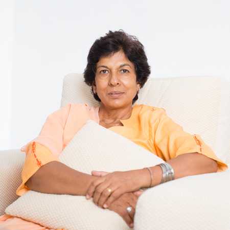 Portrait of a tired 50s Indian mature woman resting on sofa at home. Indoor senior people living lifestyle. Banque d'images