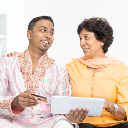 family shopping: Portrait of Indian family using internet payment at home. Mature 50s Indian woman and 30s grown son happy online shopping with credit card.