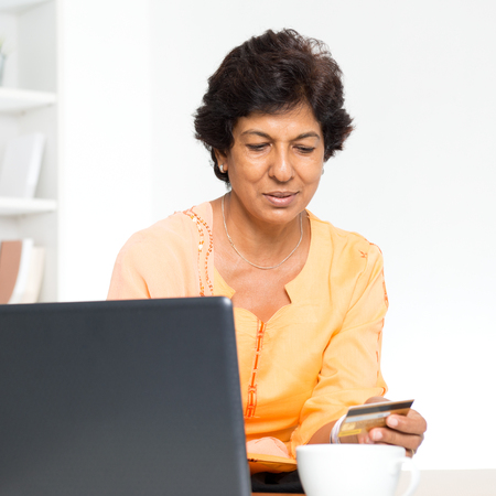 asian american: Old people and modern technology concept. Portrait of a 50s Indian mature woman hand holding credit card, using online internet payment at home. Indoor senior people living lifestyle.