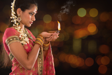 Indian woman in traditional sari lighting oil lamp and celebrating Diwali or deepavali, fesitval of lights at temple. Female hands holding oil lamp, beautiful lights bokeh background.