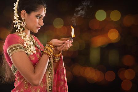 candil: Mujer india en la lámpara tradicional de aceite de iluminación sari y la celebración de Diwali o Deepavali, fesitval de las luces en el templo. Manos femeninas que sostienen la lámpara de aceite, hermosas luces bokeh. Foto de archivo