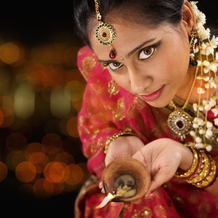 Indian female in traditional sari lighting oil lamp and celebrating Diwali or deepavali, fesitval of lights at temple. Girl hands holding oil lamp, beautiful lights bokeh background.