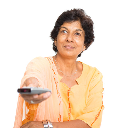 Portrait of a 50s Indian mature woman watching tv and hand holding remote control changing channel, isolated on white background. Imagens