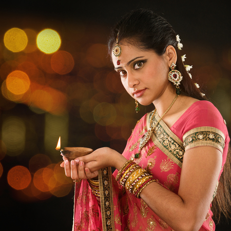 Indian girl in traditional sari lighting oil lamp and celebrating Diwali or deepavali, fesitval of lights at temple. Female hands holding oil lamp, beautiful lights bokeh background. Stock Photo